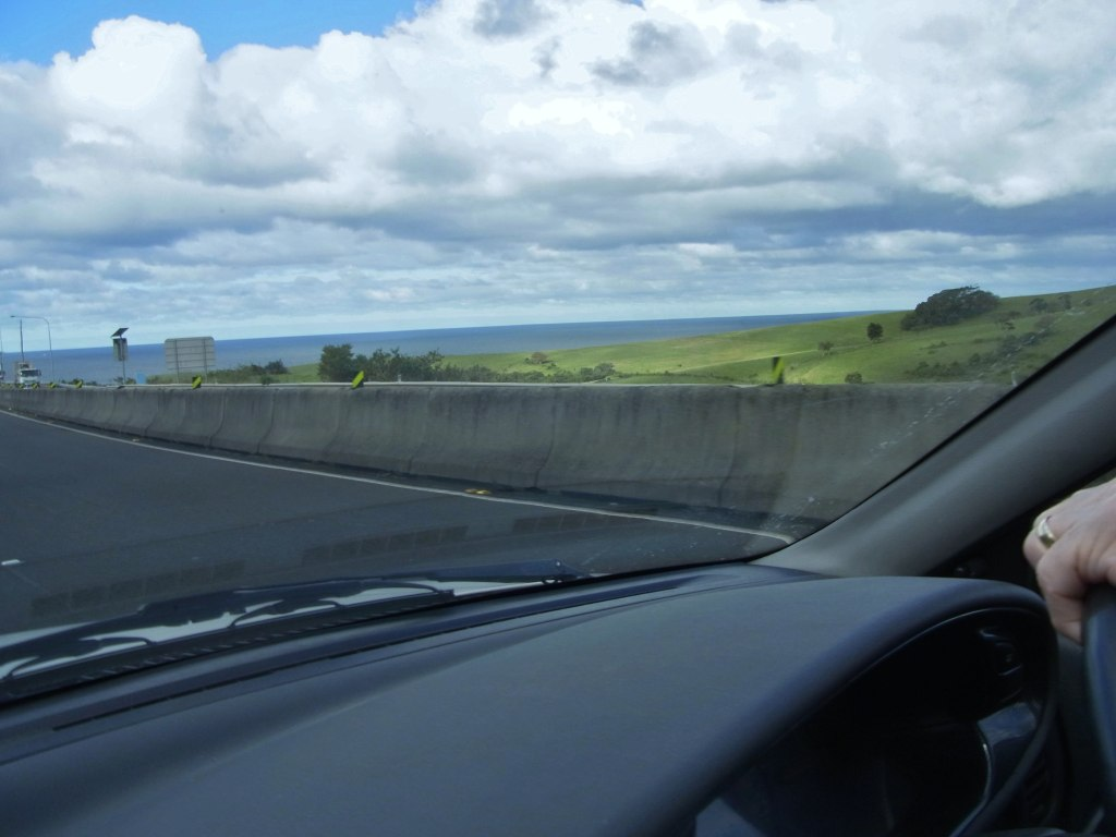 The ocean can be seen a bit to the right of the road.