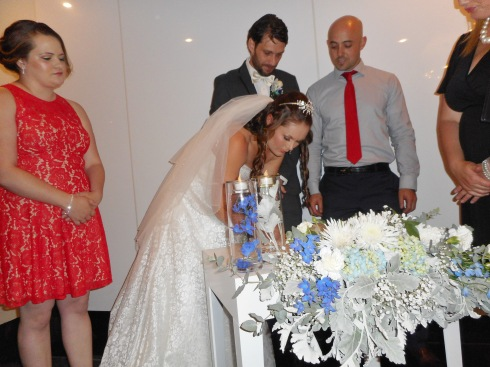 The bride signs the marriage contract in the presence of the celebrant and two witnesses.
