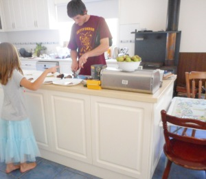 Jaki looks on as her Dad cuts up some meat for dinner.